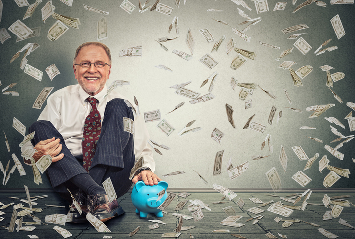 Man sitting on floor with piggy bank